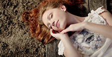 girl with luxurious red hair lies on the ground.