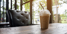 Iced cappuccino on wooden table beside in coffee