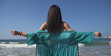 Young girl with arms outstretched standing on the beach in a thin transparent dress in the
