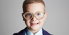 funny smiling child in glasses and siut