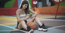 Happy smiling young sportswoman sitting on basketball court messaging online. Portrait of slim brunette Caucasian woman using smartphone outdoors after training. Sport and leisure.