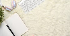 Above view of empty notebook, headphone and keyboard on white rug.